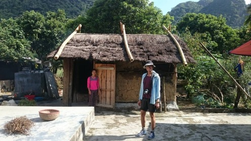 Me standing in front of a mud-walled house